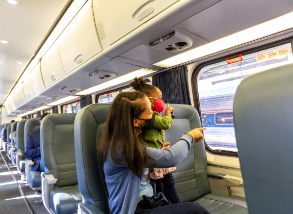 mother looking out the window and pointing with her daughter onboard amtrak in facial coverings