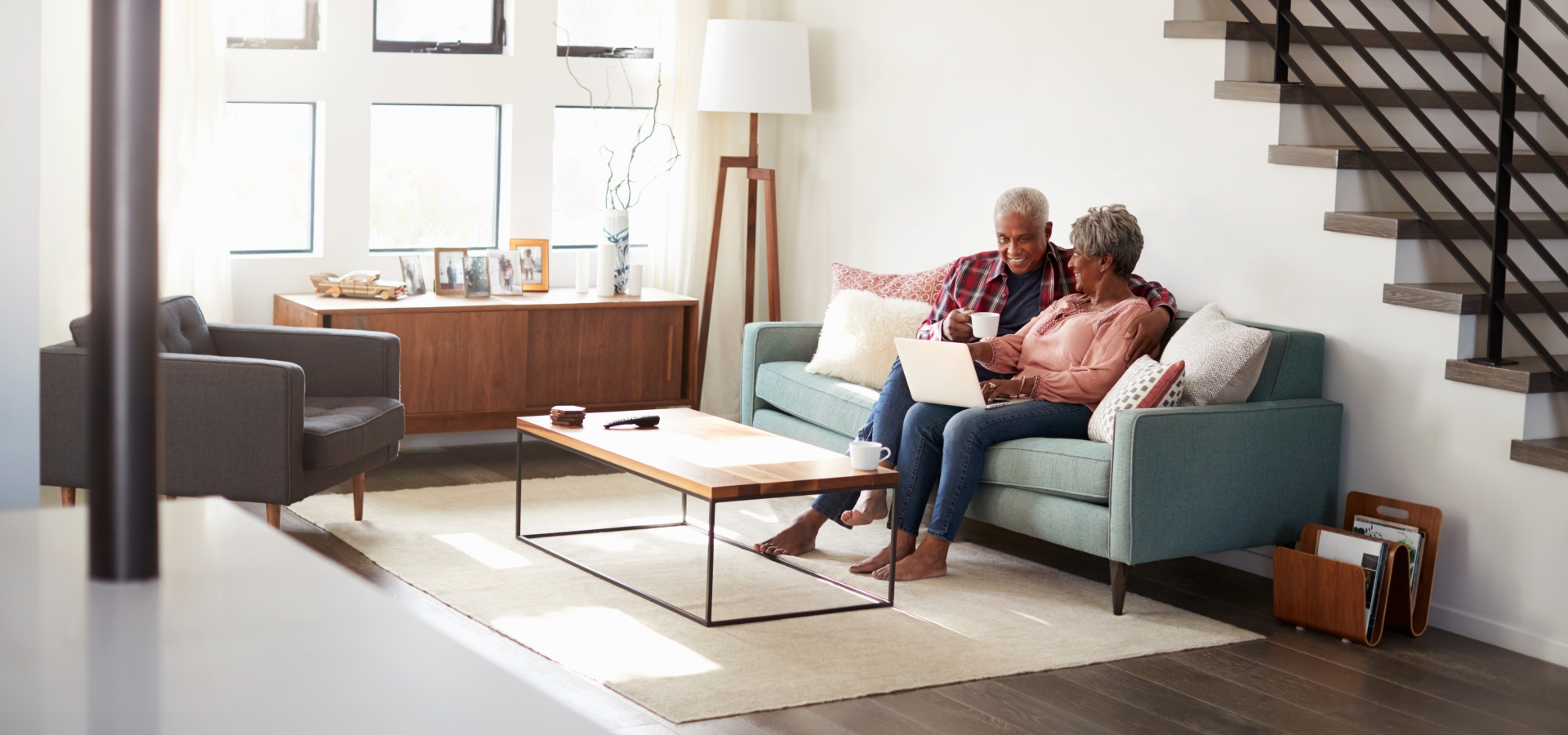 retired couple on couch looking at computer together