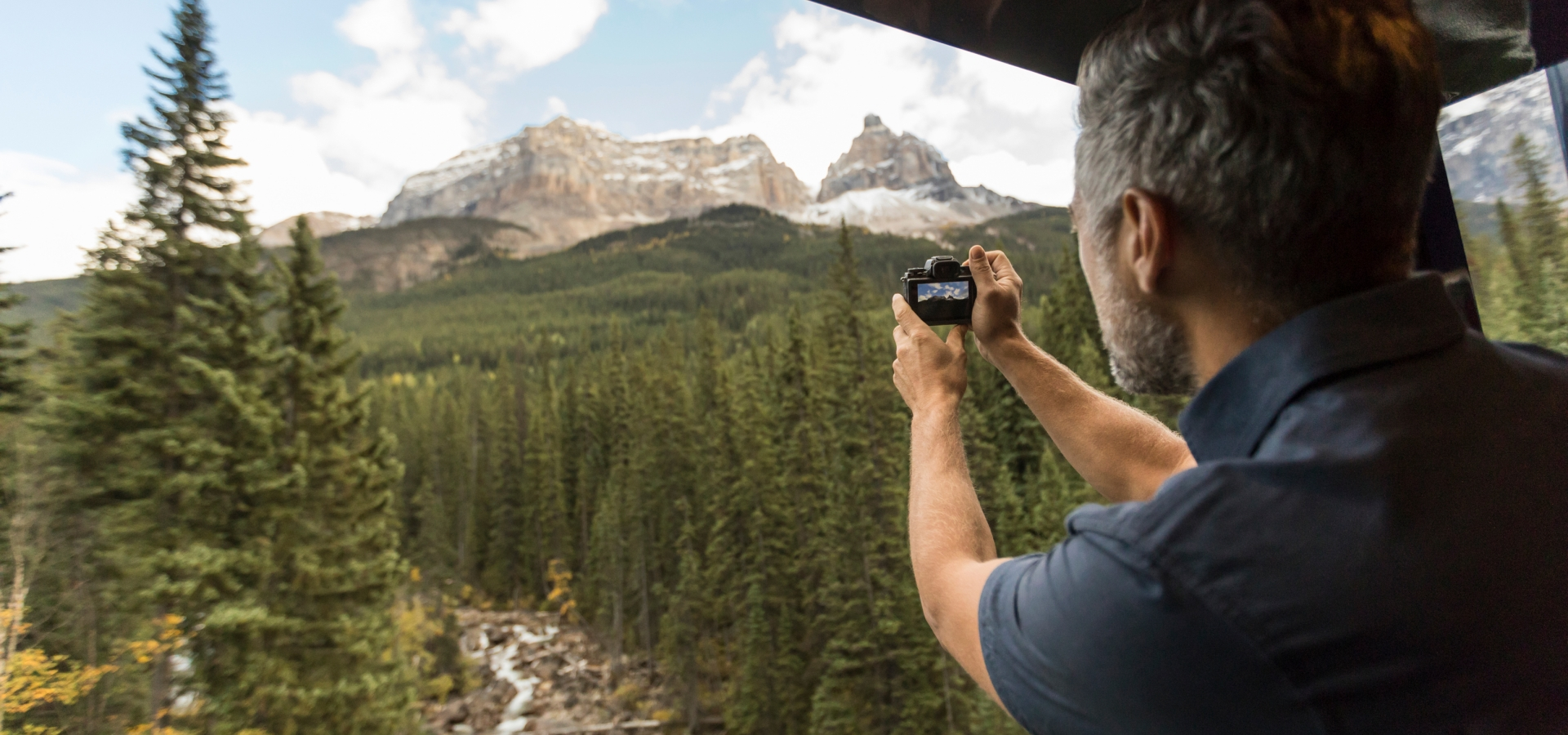 man taking picture of scenery on rocky mountaineer train
